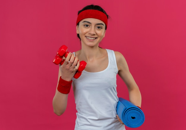Jonge fitness vrouw in sportkleding met hoofdband met halters en yogamat glimlachend vrolijk staande over roze muur