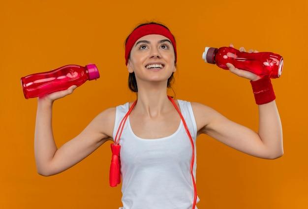 Jonge fitness vrouw in sportkleding met hoofdband met twee flessen water opzoeken met glimlach op gezicht staande over oranje muur