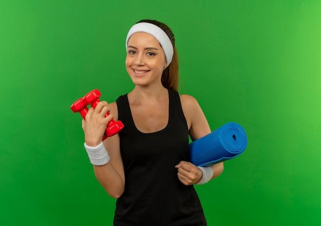 Jonge fitness vrouw in sportkleding met hoofdband met twee halters en yogamat glimlachend zelfverzekerd over groene muur