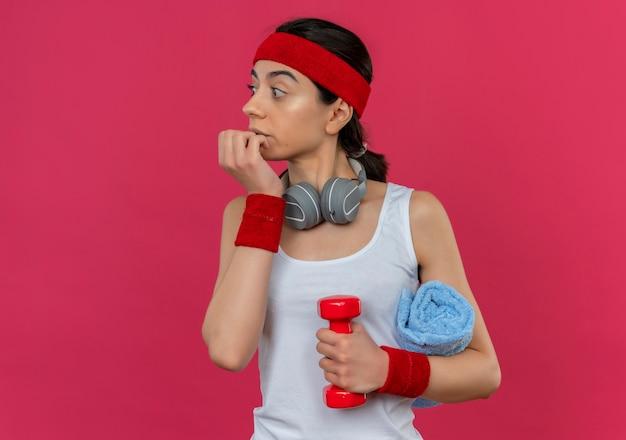 Jonge fitness vrouw in sportkleding met hoofdband met twee halters en yogamat opzij kijken bezorgd en verward nagels bijten staande over roze muur