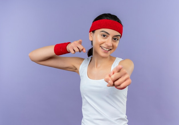 Jonge fitness vrouw in sportkleding met hoofdband met wijsvingers naar camera glimlachend vrolijk staande over paarse muur