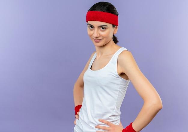 Jonge fitness vrouw in sportkleding met hoofdband met zelfverzekerde glimlach die zich over paarse muur bevindt