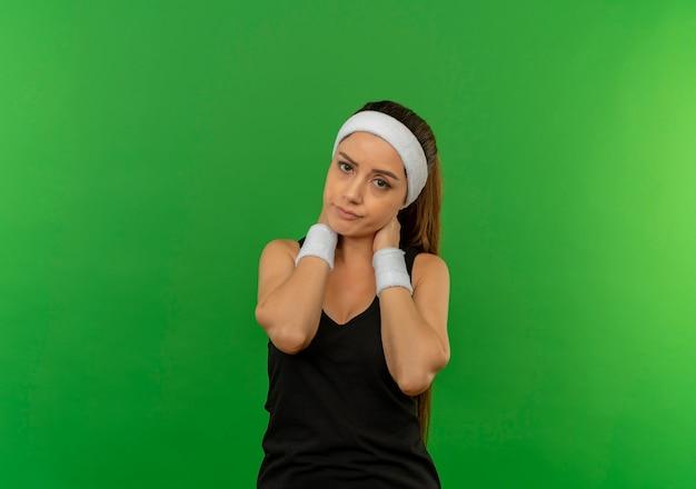 Jonge fitness vrouw in sportkleding met hoofdband onwel aanraken van haar nek met pijn staande over groene muur