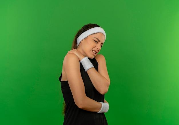 Jonge fitness vrouw in sportkleding met hoofdband onwel aanraken van haar schouder met pijn staande over groene muur