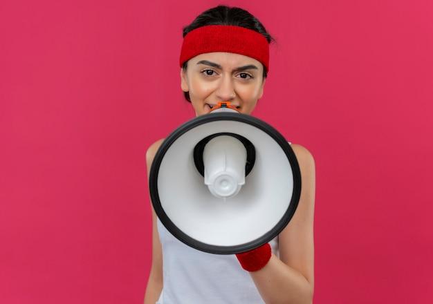 Jonge fitness vrouw in sportkleding met hoofdband schreeuwen naar megafoon met boos gezicht staande over roze muur
