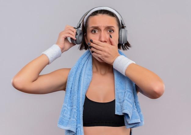 Jonge fitness vrouw in sportkleding met koptelefoon op het hoofd en een handdoek op haar nek geschokt die mond bedekken met hand die zich over witte muur bevindt