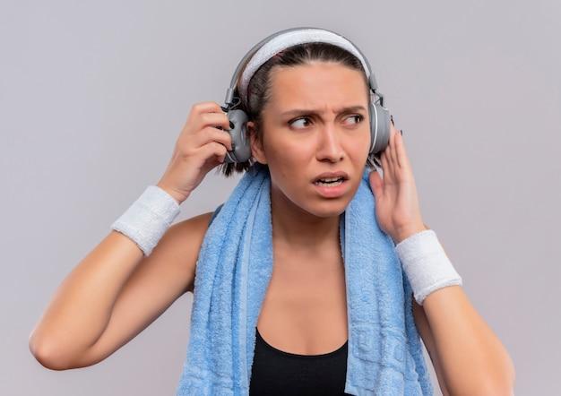 Jonge fitness vrouw in sportkleding met koptelefoon op het hoofd en handdoek op haar nek opzij kijken verward en ontevreden staande over witte muur