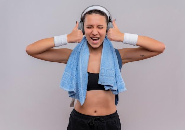 Jonge fitness vrouw in sportkleding met koptelefoon op hoofd en handdoek op haar nek gek gelukkig duimen opdagen met beide handen staande over witte muur