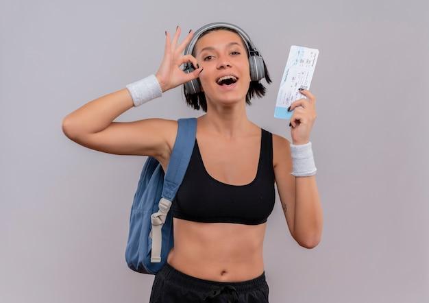 Jonge fitness vrouw in sportkleding met koptelefoon op hoofd met rugzak bedrijf vliegticket doen ok teken glimlachend vrolijk staande over witte muur