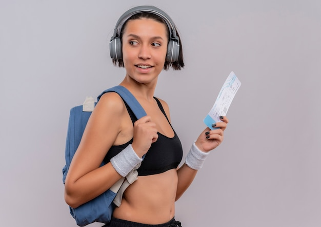 Jonge fitness vrouw in sportkleding met koptelefoon op hoofd met vliegticket opzij kijken met glimlach op gezicht staande over witte muur