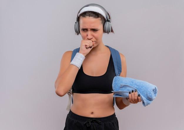 Jonge fitness vrouw in sportkleding met rugzak en koptelefoon op hoofd met handdoek opzij kijken met vuist in de buurt van kin denken staande over witte muur