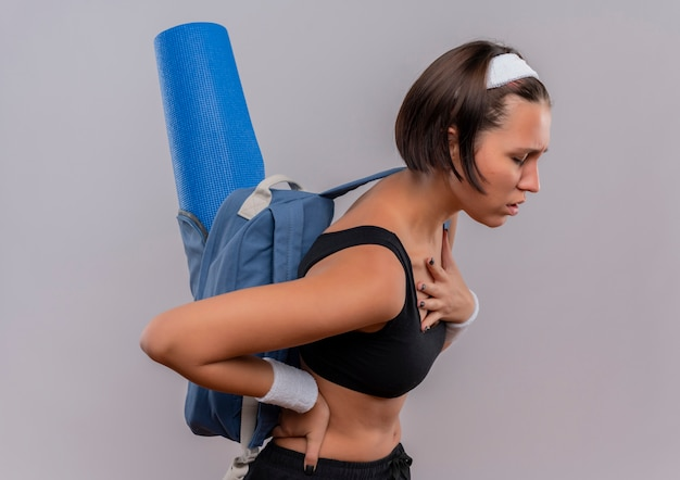 Jonge fitness vrouw in sportkleding met rugzak en yoga mat op zoek onwel hand op haar borst moe staande over witte muur