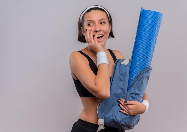 Jonge fitness vrouw in sportkleding met rugzak met yoga mat opzij glimlachend vrolijk staande over witte muur kijken