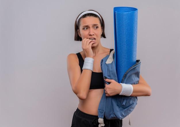Jonge fitness vrouw in sportkleding met rugzak met yogamat opzij kijken beklemtoonde en nerveuze bijtende nagels staande over witte muur