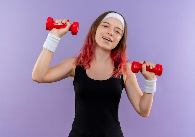 Jonge fitness vrouw in sportkleding oefeningen doen met dumbbellss glimlachend vrolijk staande over paarse muur