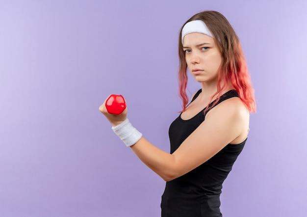 Jonge fitness vrouw in sportkleding oefeningen doen met halter met ernstig gezicht staande over paarse muur