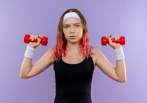 Jonge fitness vrouw in sportkleding oefeningen doen met halters met ernstig gezicht staande over paarse muur