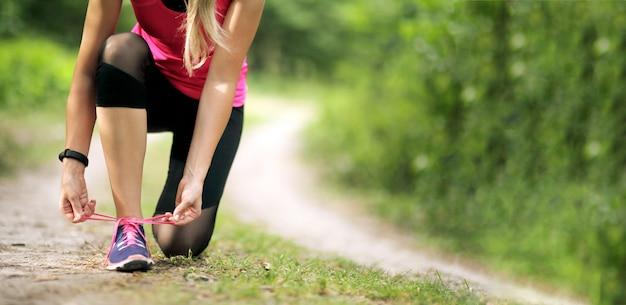 Jonge fitness vrouw koppelverkoop schoenveter met sneakers. gezond fit leven.