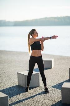 Jonge fitness vrouw loper benen uitrekken voordat run