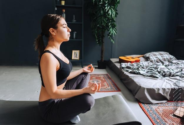 Jonge fitness vrouw mediteren, yoga binnenshuis thuis in de buurt van het bed doen