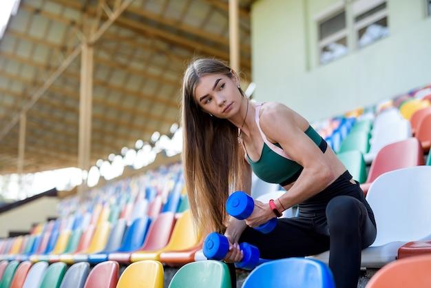 Jonge fitness vrouw uit te werken met halters in het stadion van de stad. sport concept