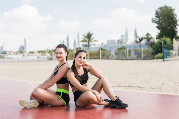Jonge fitness vrouwen die in sportkleren op het strand in openlucht zitten
