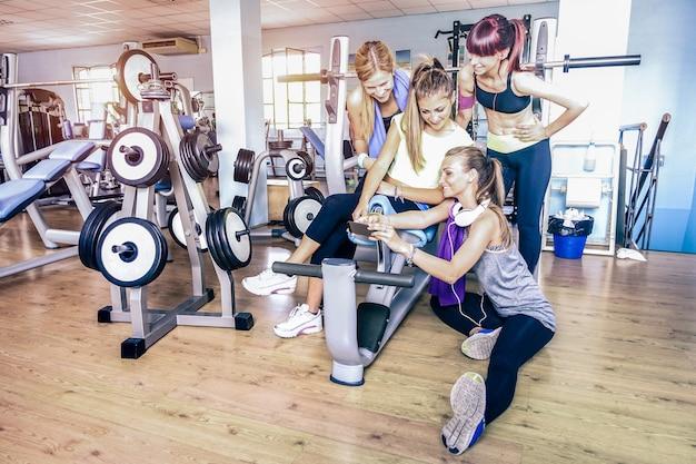 Jonge fitness vrouwen die selfie met smartphone bij gymnastiekclub nemen