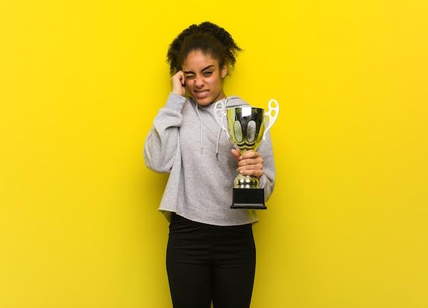 Jonge fitness zwarte die oren behandelt met handen. met een trofee.