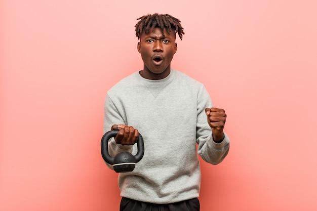 Jonge fitness zwarte man met een halter juichen zorgeloos en opgewonden. overwinning concept.