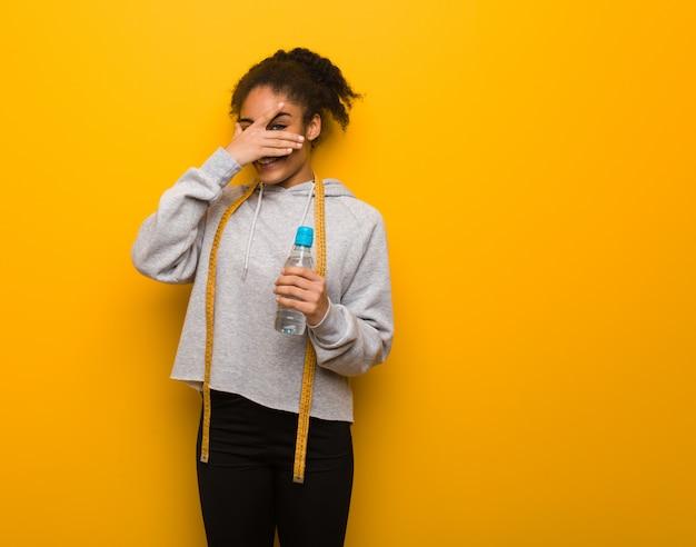Jonge fitness zwarte vrouw beschaamd en lachen tegelijkertijd. een fles water houden.