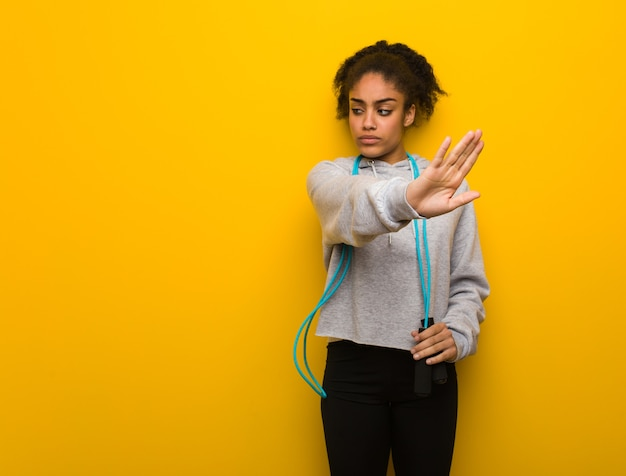 Jonge fitness zwarte vrouw die hand op de voorgrond zet. een springtouw vasthouden.