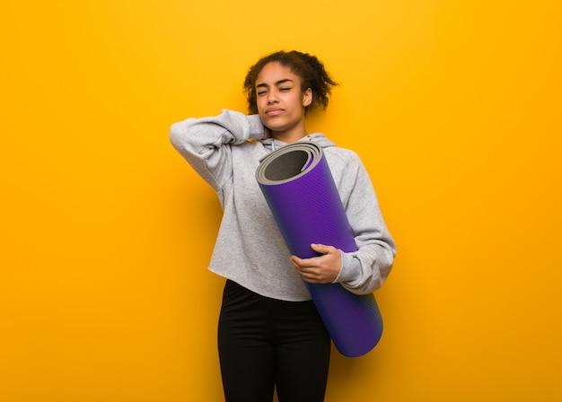 Jonge fitness zwarte vrouw die nekpijn lijdt. een mat vasthouden.
