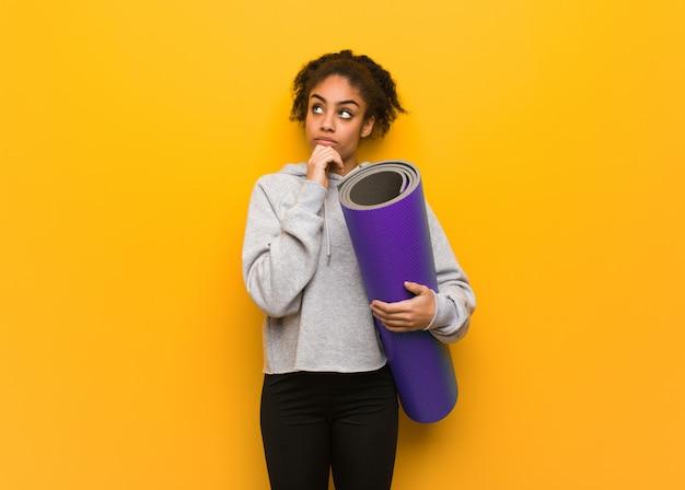 Jonge fitness zwarte vrouw die over een idee denkt. een mat vasthouden.
