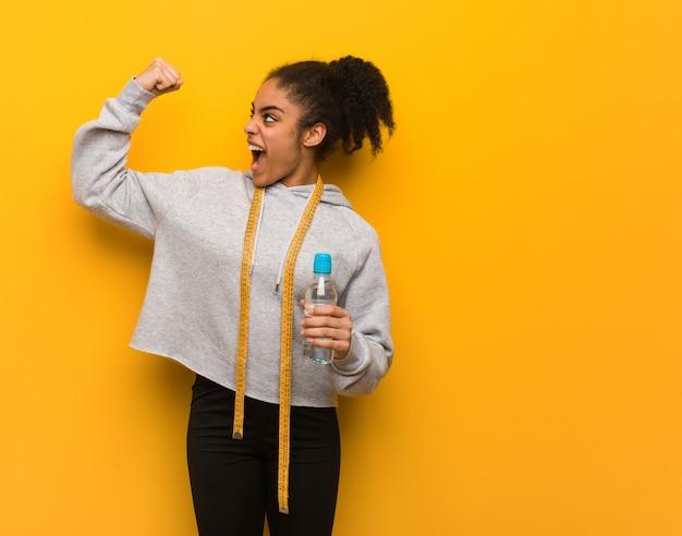 Jonge fitness zwarte vrouw die zich niet overgeeft. een fles water houden.