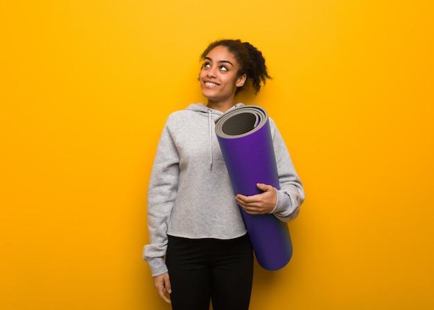 Jonge fitness zwarte vrouw dromen van het bereiken van doelen en doeleinden. een mat vasthouden.
