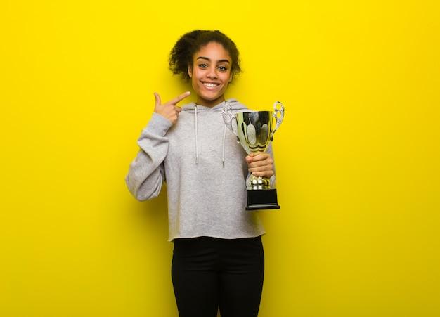 Jonge fitness zwarte vrouw glimlacht, wijzend op mond. met een trofee.