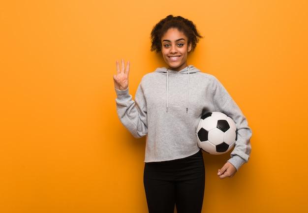 Jonge fitness zwarte vrouw met nummer drie. een voetbal vasthouden.