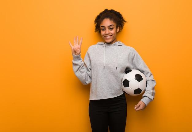 Jonge fitness zwarte vrouw met nummer vier. een voetbal vasthouden.
