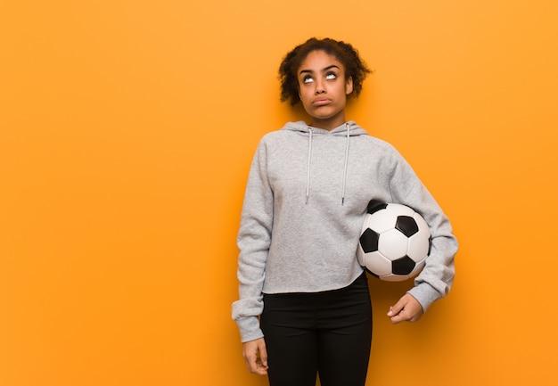 Jonge fitness zwarte vrouw moe en verveeld. een voetbal vasthouden.