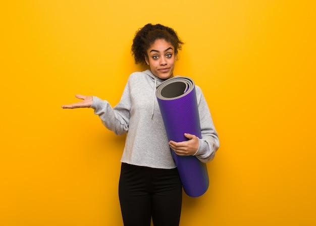 Jonge fitness zwarte vrouw twijfelen en schouders ophalen