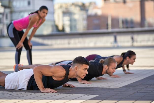 Jonge fitnessmannen en -vrouwen die push-ups doen in de stad