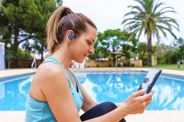 Jonge fitnessvrouw die buiten een online sportklasse kiest. horizontaal zijaanzicht van een jonge vrouw die verbinding maakt met technologie naar een gymles met vrienden naast een zwembad.