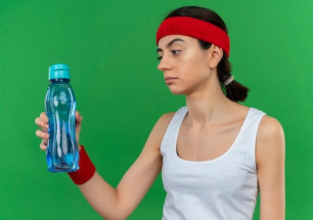 Jonge fitnessvrouw in sportkleding met hoofdband die fles water houdt die ernaar kijkt ontevreden met sceptische uitdrukking die zich over groene muur bevindt