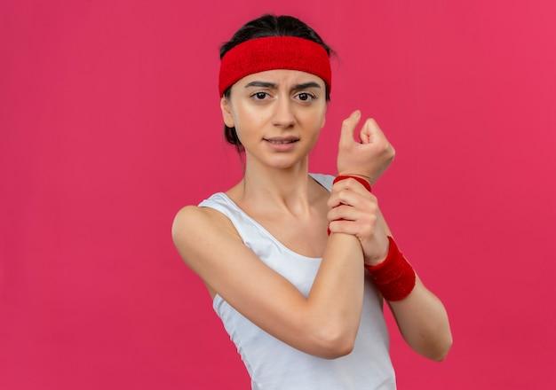 Jonge fitnessvrouw in sportkleding met hoofdband die onwel kijkt wat betreft haar pols met pijn die zich over roze muur bevindt