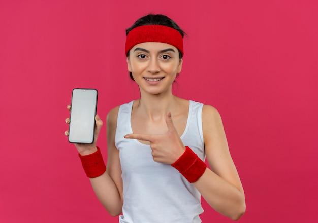 Jonge fitnessvrouw in sportkleding met hoofdband die smartphone toont die met wijsvinger ernaar richt glimlachend zelfverzekerd over roze muur