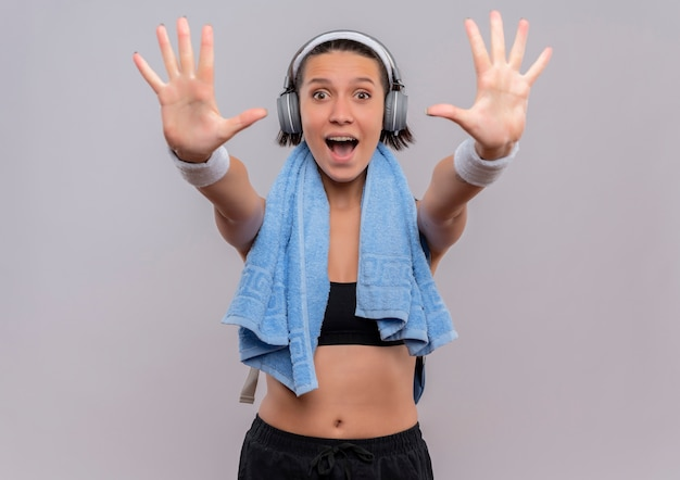 Jonge fitnessvrouw in sportkleding met koptelefoon op het hoofd en een handdoek om haar nek die haar handpalmen uitstrekt met nummer tien glimlachend blij en opgewonden staande over witte muur