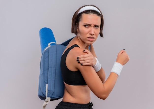 Jonge fitnessvrouw in sportkleding met rugzak en yogamat die onwel kijkt wat betreft haar schouder die pijn voelt die zich over witte muur bevindt