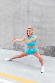 Jonge fitnessvrouw met draadloze koptelefoon in sportkleding die buiten traint in de buurt van grijze muur op straat