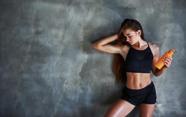 Jonge fitnessvrouw met een slank lichaam en een fles water leunt op de muur.