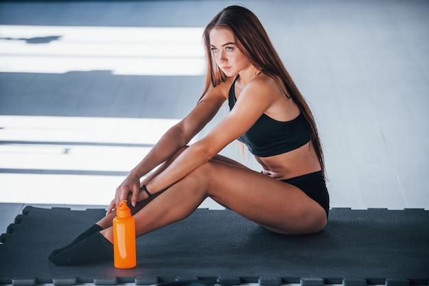 Jonge fitnessvrouw met een slank lichaamstype zit op de mat met een fles water.